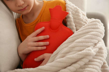 Ill boy with hot water bottle suffering from cold at home, closeup Foto de archivo