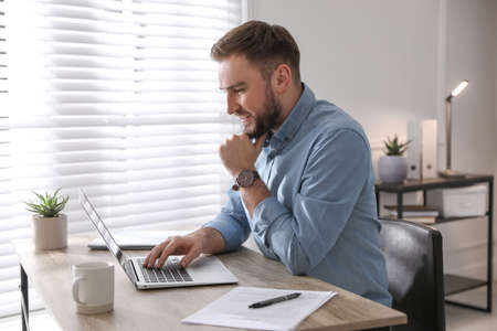 Young man working on laptop at table in office Imagens