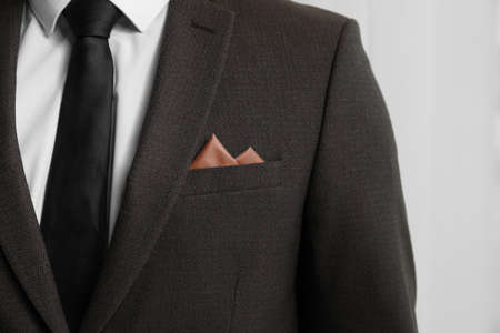 Man with handkerchief in pocket of his suit on light background, closeup