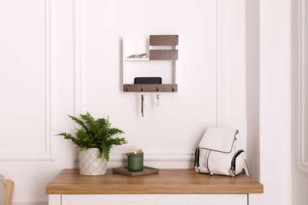 Wooden hanger for keys on white wall in hallway
