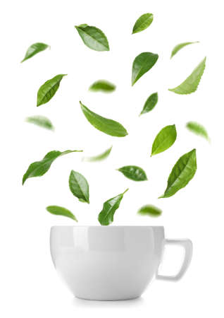 Cup of hot tea and falling green leaves on white background Banque d'images