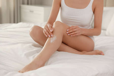 Young woman applying body cream onto her leg at home, closeup