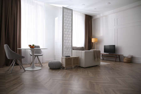 Modern living room with parquet floor and stylish furniture