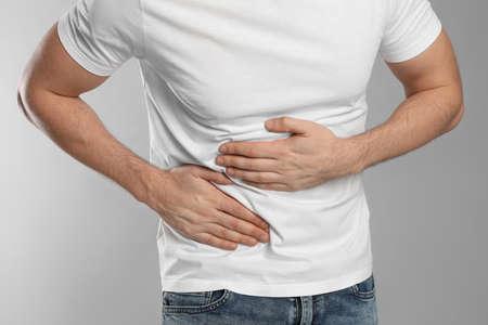 Man suffering from pain in lower right abdomen on light grey background, closeup. Acute appendicitis