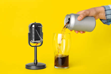 Woman making ASMR sounds with microphone and soda drink on yellow background, closeup