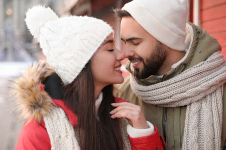 Happy young couple spending time together at winter fair. Christmas celebration