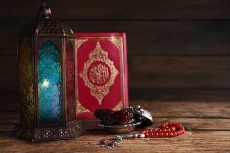 Composition with Arabic lantern and quran on wooden table. Space for text