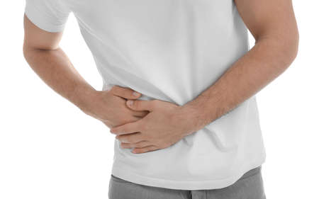 Man suffering from pain in lower right abdomen on white background, closeup. Acute appendicitis