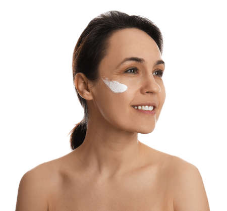 Woman with cream on face against white background