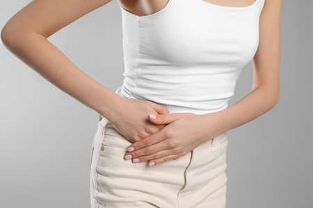 Woman suffering from appendicitis inflammation on grey background, closeup Archivio Fotografico