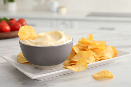 Potato chips and mayonnaise on white marble table