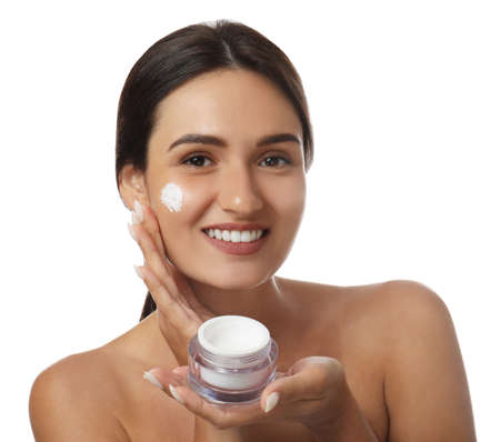 Young woman holding jar of facial cream on white background