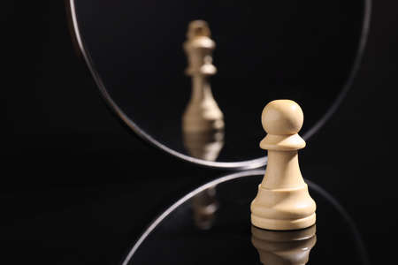Pawn feeling itself like queen, chess piece in front of mirror. Self-appraisal, alter ego, true personality concepts