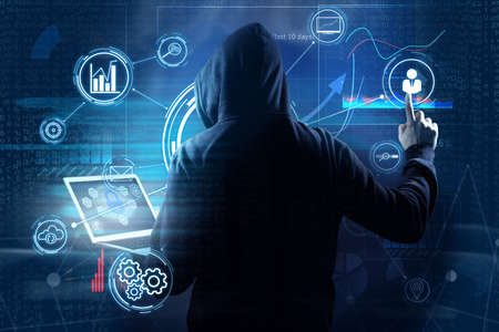 Man in hood with laptop and digital icons on dark background. Cyber attack concept Stock Photo