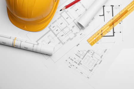 Flat lay composition with blueprints and hardhat on white background