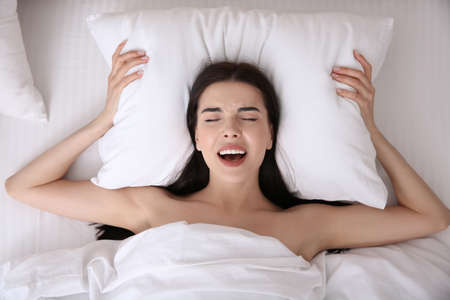Young woman having in bed, top view