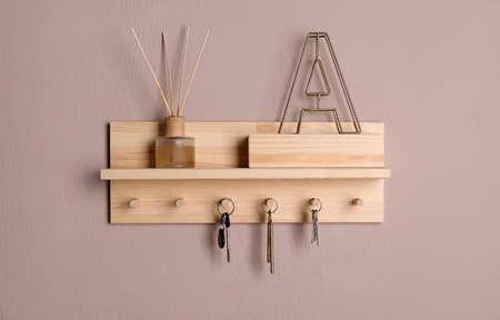 Wooden hanger for keys on color wall Standard-Bild