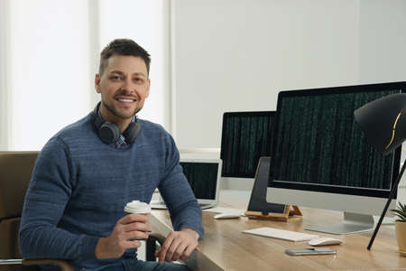 Happy programmer with headphones and coffee working at desk in office