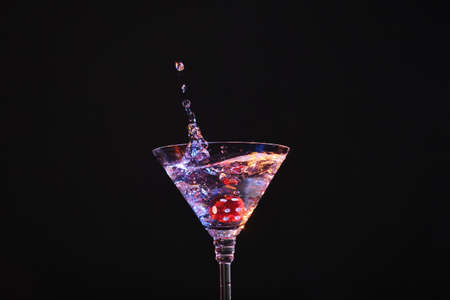 Casino dice falling into glass of alcohol drink on black background