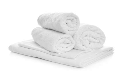 Rolled towels and folded bedding on white background Stock Photo