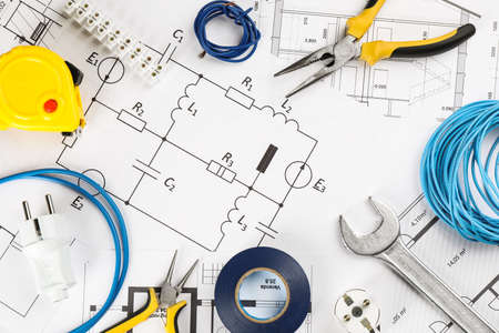 Flat lay composition with electrician's tools on house plan sheets Фото со стока