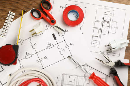 Flat lay composition with electrician's tools and house plan sheets on table