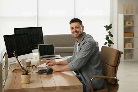 Happy programmer working at desk in office