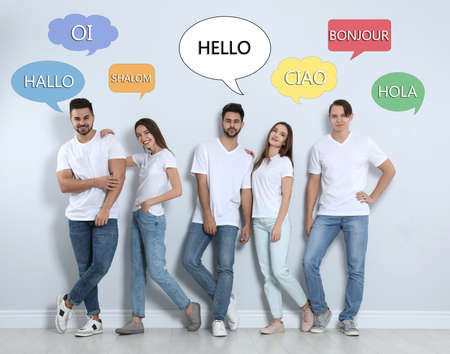 Happy people posing near light wall and illustration of speech bubbles with word Hello written in different languages Zdjęcie Seryjne