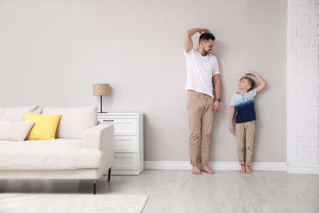 Father and son comparing their heights near wall in living room Stock Photo