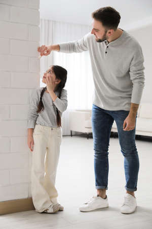 Father measuring daughter's height near white brick pillar at home