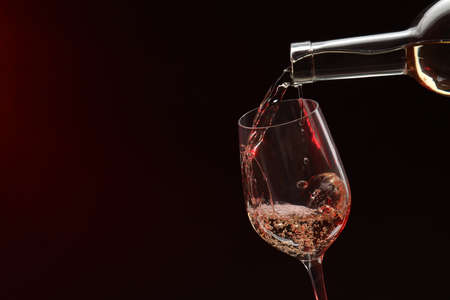 Pouring white wine from bottle into glass on dark background, space for text