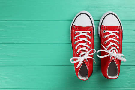 Pair of red sneakers on turquoise wooden table, flat lay. Space for text
