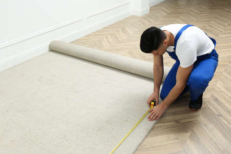 Worker with measuring tape installing new carpet indoors