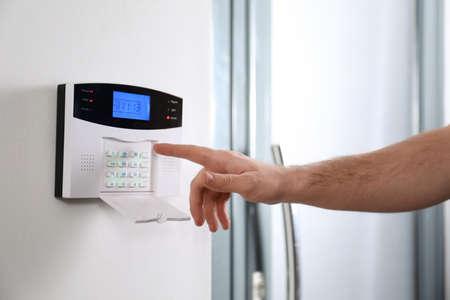 Man entering code on home security system near door, closeup Stockfoto