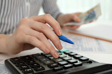 Woman counting money with calculator at table, closeup