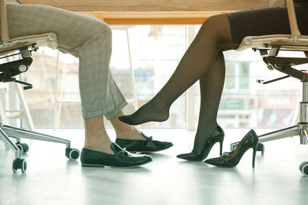Woman flirting with his colleague during work in office, closeup. Cheating concept Standard-Bild