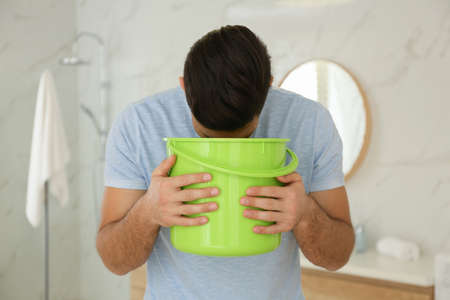 Man with bucket suffering from nausea in bathroom. Food poisoning