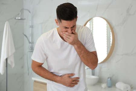 Man suffering from nausea in bathroom. Food poisoning Stockfoto