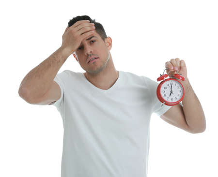 Emotional man with alarm clock on white background. Being late because of oversleeping