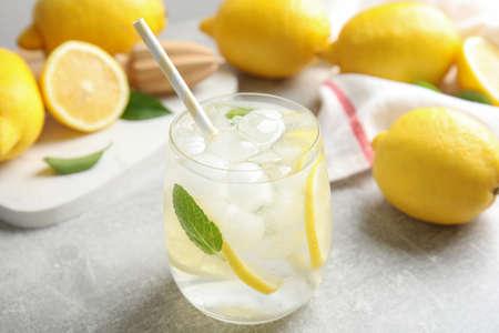 Glass of cold lemonade on light grey table, closeup
