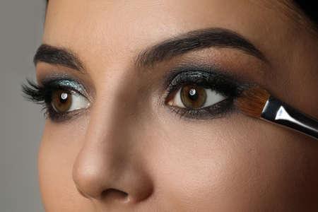 Applying dark eye shadow with brush onto woman's face, closeup. Beautiful evening makeup Imagens