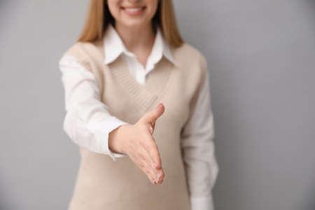 Woman offering handshake on light grey background, closeup