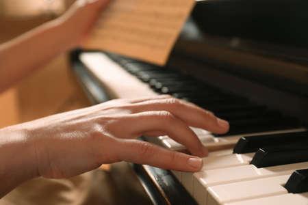 Young woman playing piano, closeup. Music lesson Foto de archivo