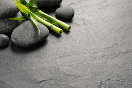 Spa stones and bamboo stems on grey table. Space for text Stock Photo