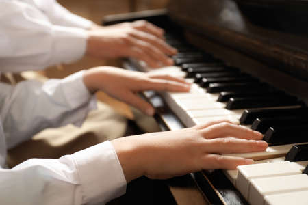 Young woman with child playing piano, closeup. Music lesson Stock Photo