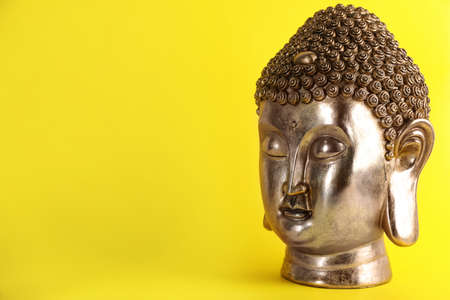 Beautiful golden Buddha sculpture on yellow background. Space for text