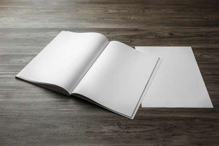 Sheet of paper and blank brochure on wooden table. Mockup for design