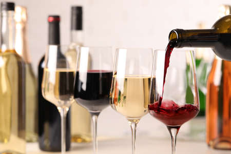 Pouring red wine from bottle into glass, closeup Stock Photo