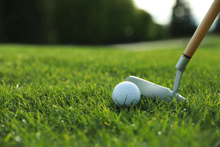 Hitting golf ball with club on green course, closeup. Space for text Stockfoto