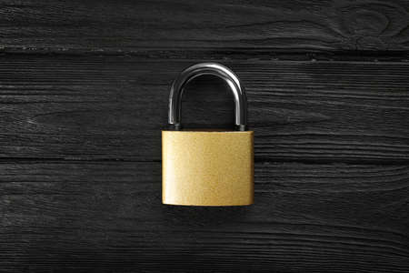 Modern padlock on black wooden table, top view